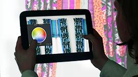 Eine Benutzerin ändert mittels einer Mobile-Augmented-Reality-Anwendung die Farbe von Gardinen auf einem Tablet.
