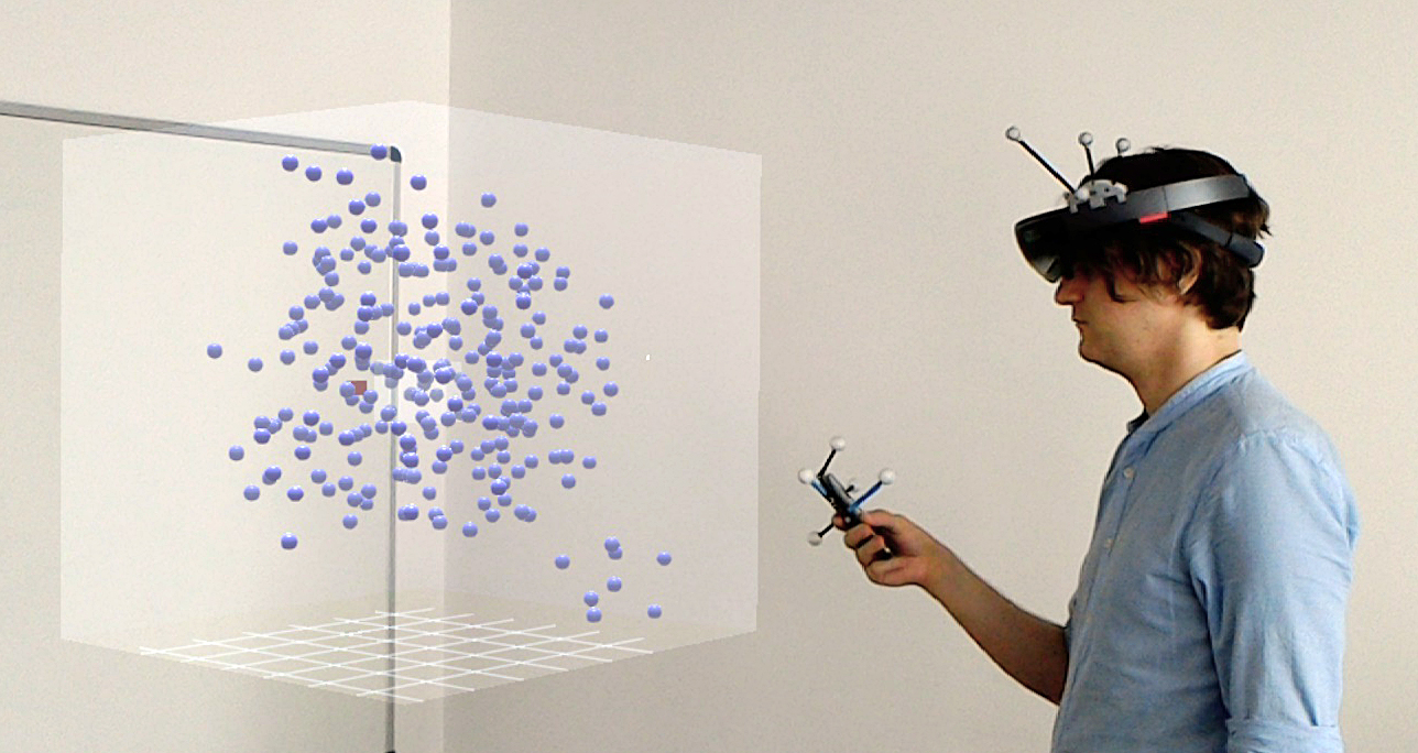 A photo of a user wearing a HoloLens and using a smartphone to explore an AR data set.